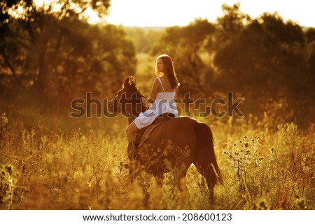 Young woman riding a horse at sunset - stock photo