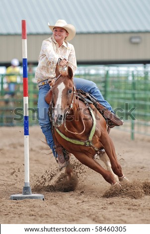 Young woman riding a horse in a pole bending race at a rodeo. - stock photo