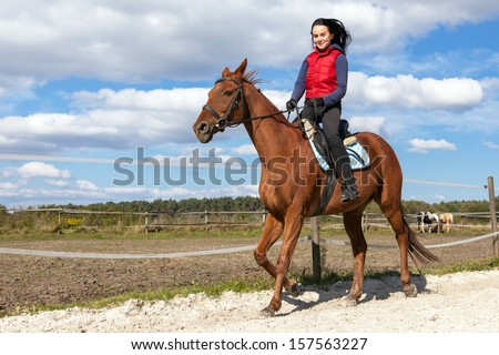Young woman riding a horse in the countryside - stock photo