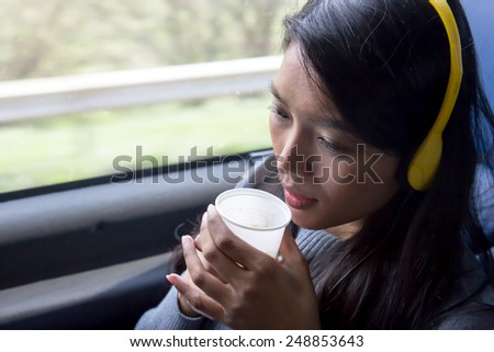 young woman riding on the bus and drinking coffee - stock photo