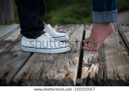 Young woman rises up on tiptoes to kiss lover - stock photo