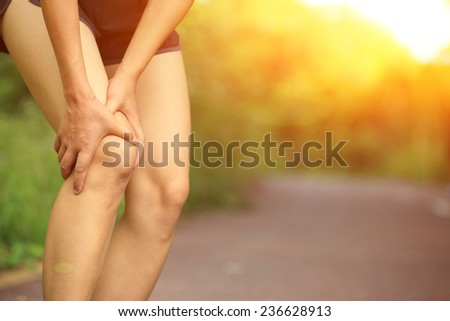 young woman runner hold her injured leg  - stock photo