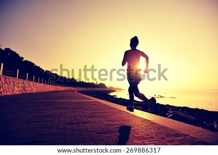 young woman runner running at seaside. woman fitness silhouette sunrise jogging workout wellness concept.  - stock photo