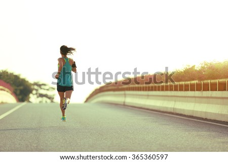 young woman runner running on city bridge road - stock photo