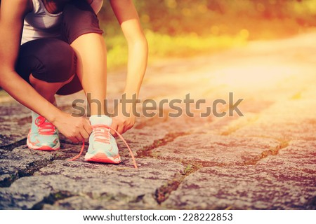 young woman runner tying shoelaces on country road  - stock photo