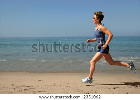 Young woman running alone on the beach - stock photo