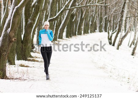 Young woman running at the park. Caucasian smiling girl jogging at winter morning. Image with copy space - stock photo