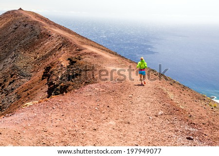 Young woman running in mountains on sunny summer day. Beautiful landscape sea ocean and female runner jogging and exercising outdoors in nature, rocky trail footpath on La Palma, Canary Islands Spain - stock photo
