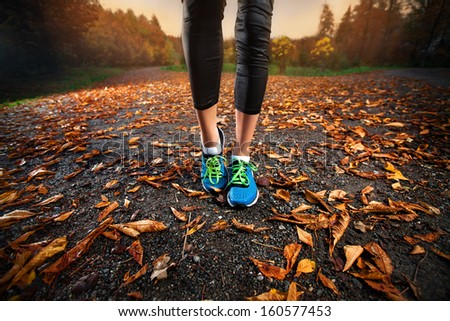 young woman running in the early evening autumn leaves - stock photo