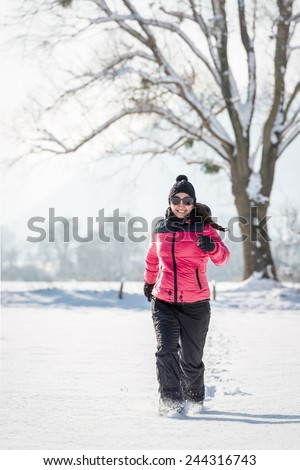 Young woman running in the snow in winter - stock photo