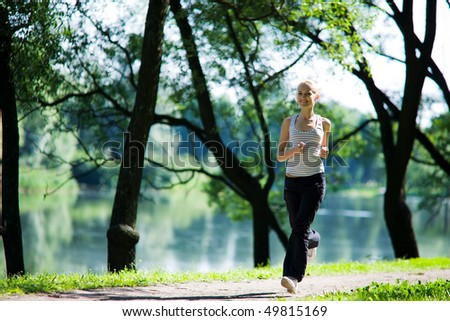 Young woman Running looking straight summer morning - stock photo