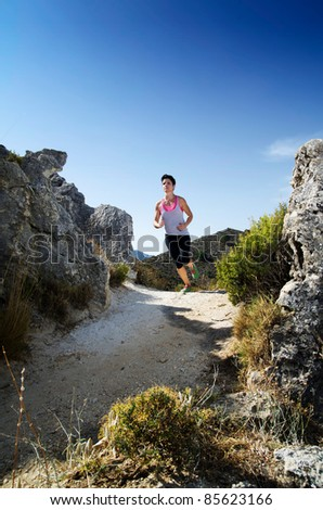 Young woman running on a mountain path. - stock photo