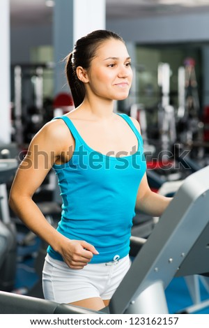 young woman running on a treadmill, exercise at the fitness club - stock photo