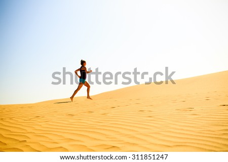 Young woman running on beautiful inspirational desert dunes on sunny summer day. Beauty female runner jogging and exercising outdoors in nature Gran Canaria, Canary Islands - stock photo