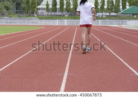 Young woman  running on racetrack during training session. Asian girl  runner practicing on athletics race track. - stock photo