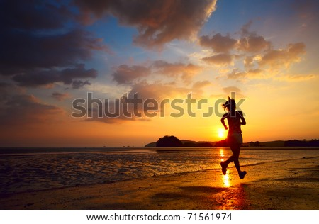 Young woman running on sea coast at sunset - stock photo
