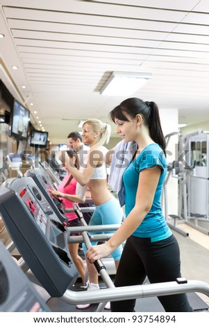 young woman running on treadmill at gym - stock photo