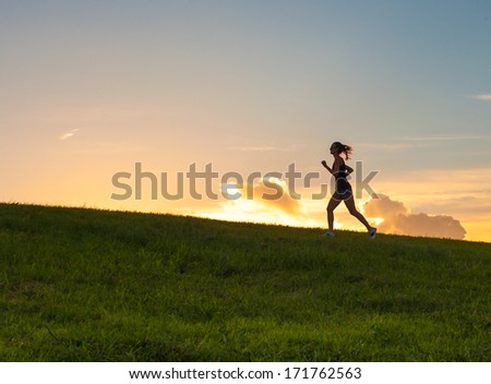 Young woman running outdoor during sunset - stock photo