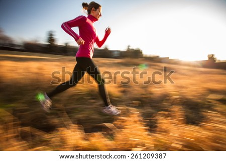 Young woman running outdoors on a lovely sunny winter/fall day (motion blurred image) - stock photo