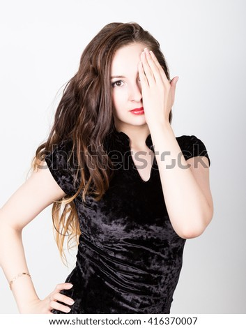 young woman's portrait with different happy emotions. girl closed her eyes with his hand - stock photo