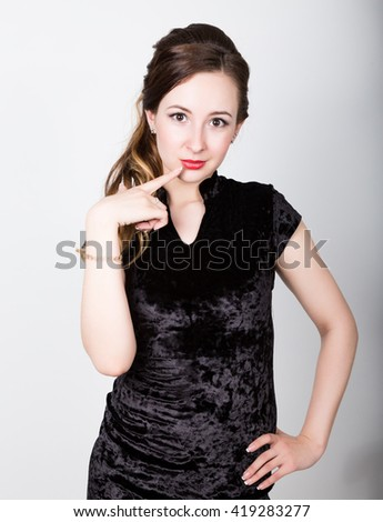 young woman's portrait with different happy emotions. she raised an index finger to his lips - stock photo