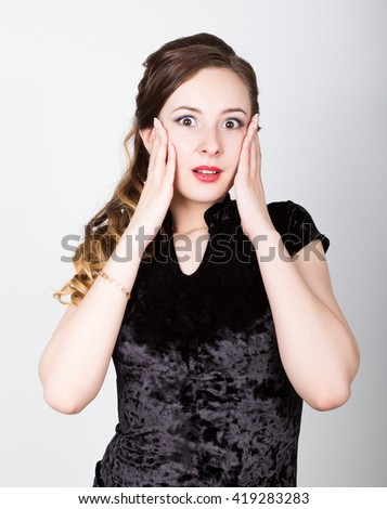 young woman's portrait with different happy emotions. she took his head with his hands. surprise - stock photo