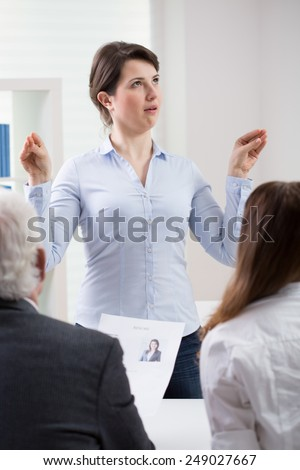 Young woman's ridiculous behavior on job interview - stock photo