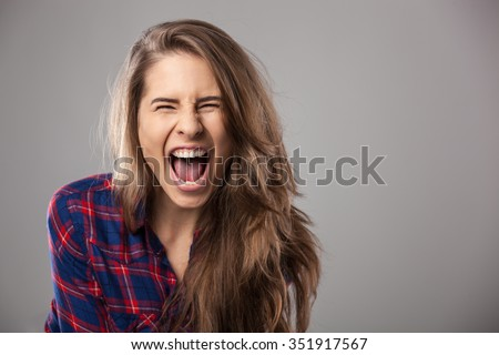 Young woman screaming loudly - studio portrait. - stock photo