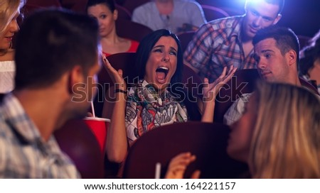 Young woman screaming with horror in movie theater, others watching. - stock photo