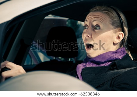 Young woman screams while driving a car - stock photo