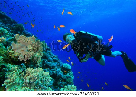 Young Woman Scuba Diver on coral reef in clear blue water - stock photo