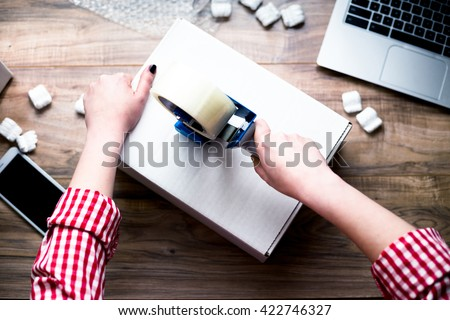 Young woman sealing a box with tape. Preparing for moving. Packing, selling online, shipping, moving and lifestyle concept - stock photo