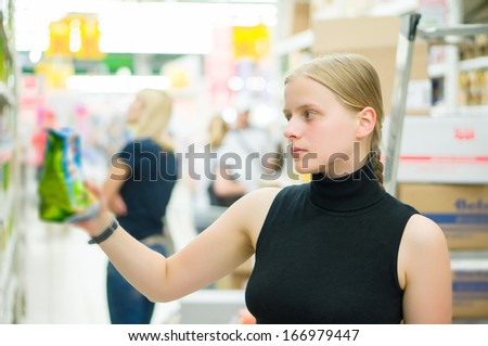 Young woman select bakery products in supermarket - stock photo