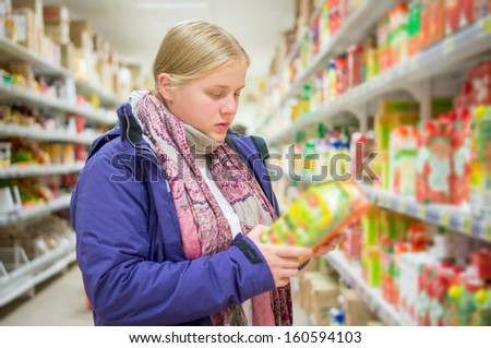 Young woman select juices on shelves in supermarket - stock photo