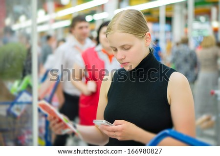 Young woman select sea food  products in supermarket - stock photo