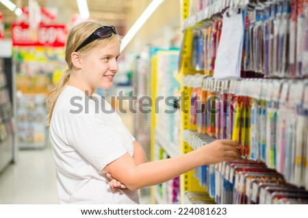 Young woman select writing tools in stationery department in supermarket - stock photo