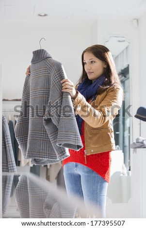 Young woman selecting sweater in store - stock photo