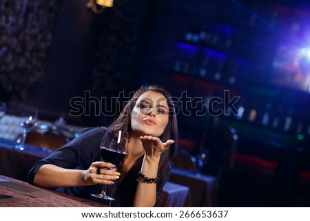 Young woman sending a romantic blow kiss in nightclub - stock photo