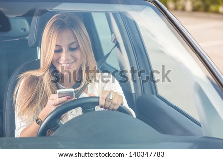 Young Woman Sending Messages while Driving - stock photo