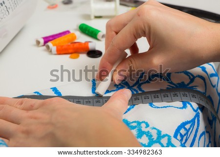 Young woman sewing on a sewing machine a garment - stock photo
