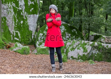 Young woman shivering with cold and embracing herself on a forest wearing a red overcoat, a beanie and gloves during winter  - stock photo