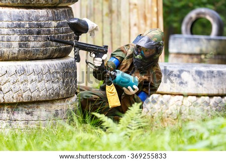Young woman shooting from paintball gun - stock photo