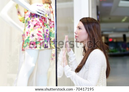 Young woman shopping at the mall for a dress or skirt, looking at a store window - stock photo