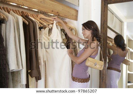 Young woman shopping for clothes in a fashion store. - stock photo