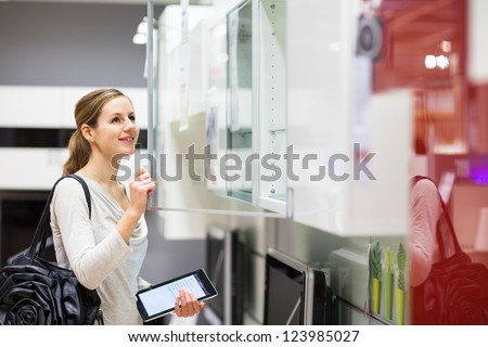 Young woman shopping for furniture in a furniture store, using her tablet computer to compare prices/check for dimensions - stock photo
