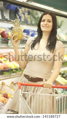 Young woman shopping for groceries at the supermarket - stock photo