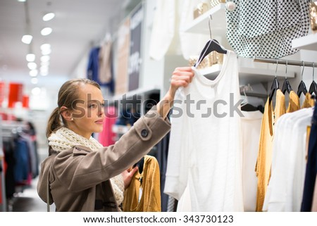 Young woman shopping in a fashion store (color toned image; shallow DOF) - stock photo