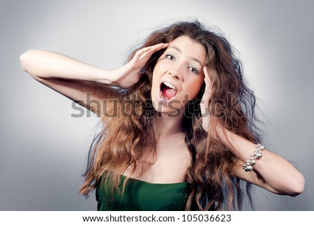 young woman shout and scream holding her hands on her head - stock photo