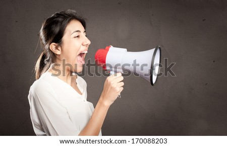 young woman shouting with a megaphone on a gray background - stock photo