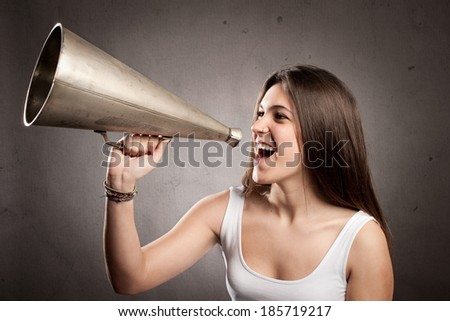 young woman shouting with an old megaphone on a gray background - stock photo